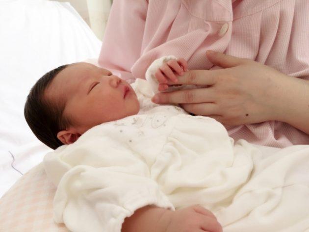 ママの手を握る新生児